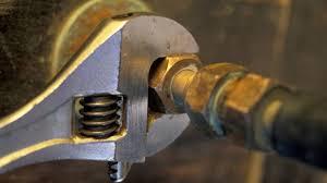 un plombier serre un écrou sur une canalisation pour la raccorder